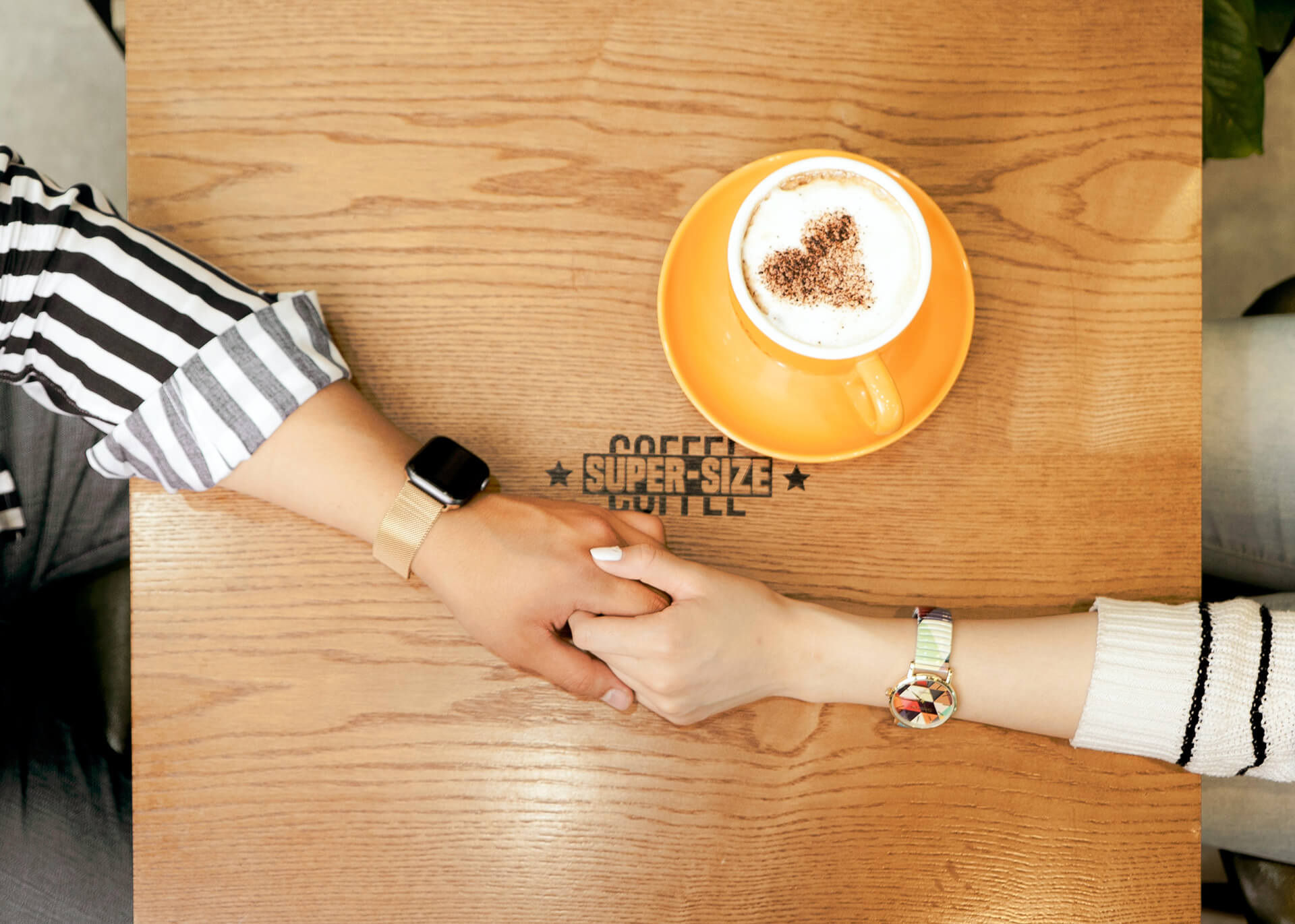 couple holding hands in a cafe