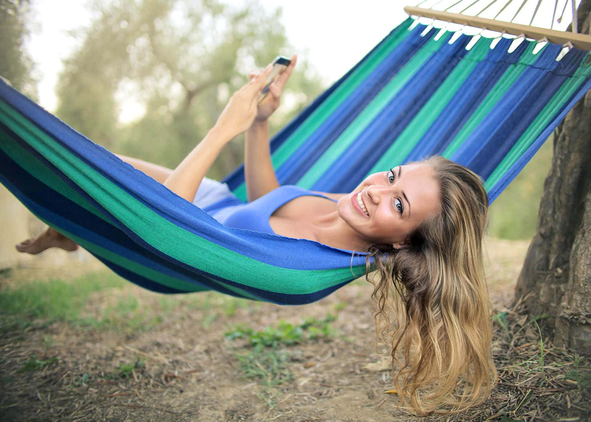 woman in a hammock with a phone texting