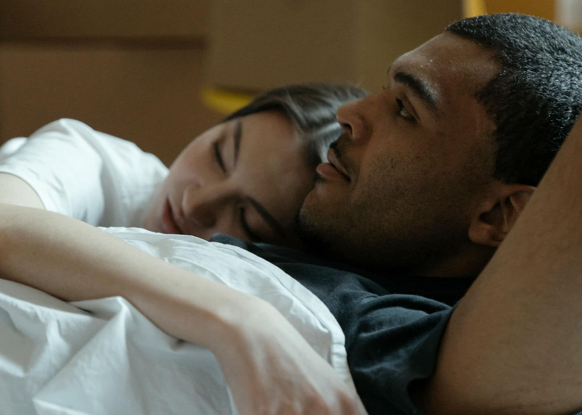 couple in bed with woman sleeping