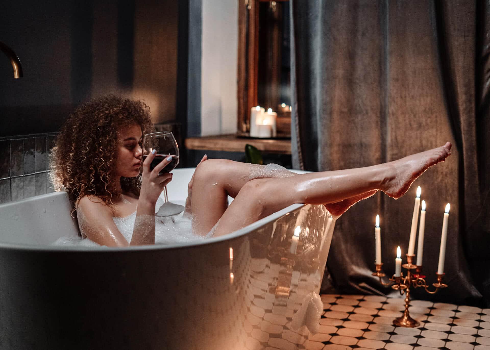 woman in bathtub holding wine glass