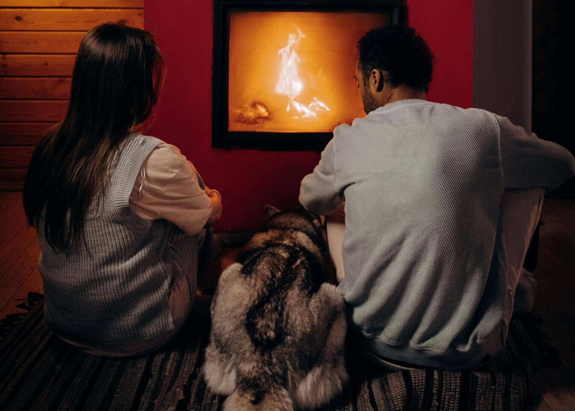 couple with a dog in front of fireplace