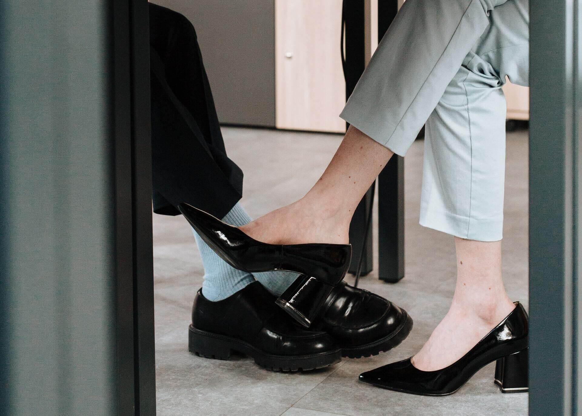 man an woman legs under the table
