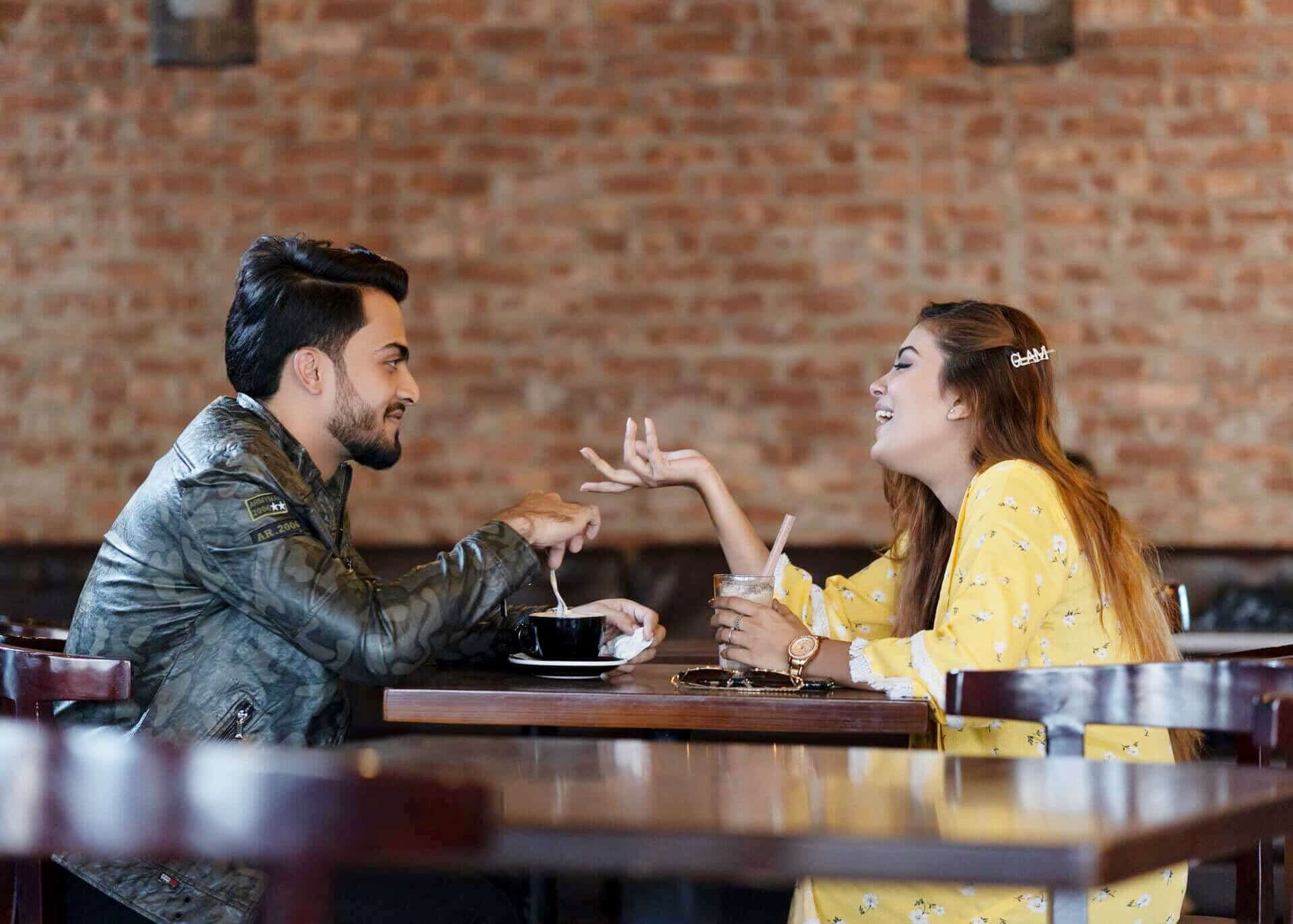 man and woman chatting in a cafe