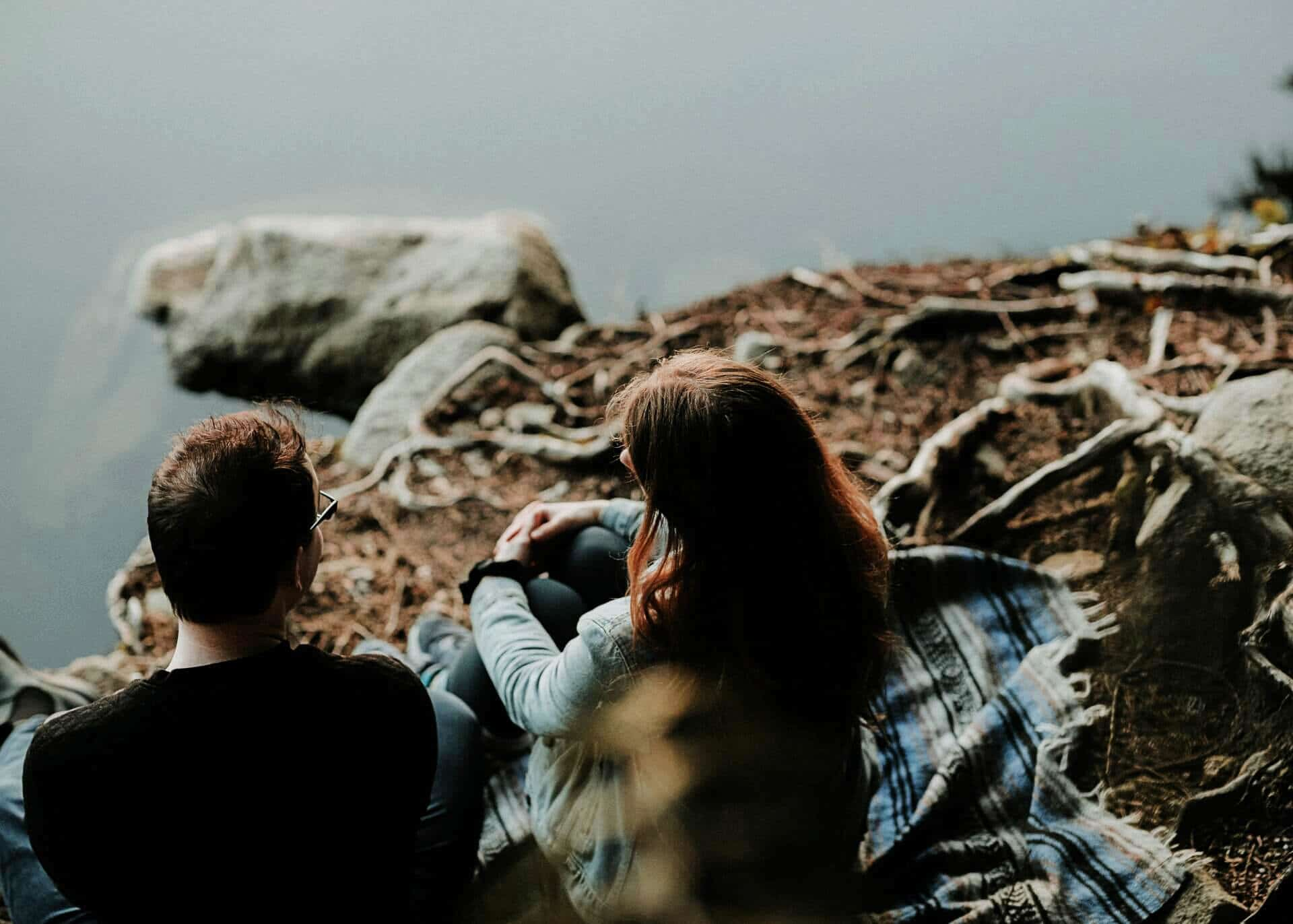 two people sitting on a cliff talking